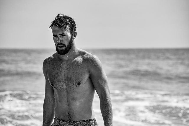 Black and white depiction of a man by the sea with a shorter beard.