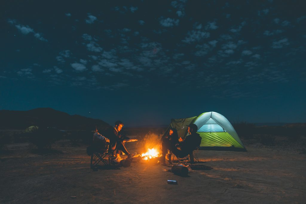 Two people sitting near a campfire.