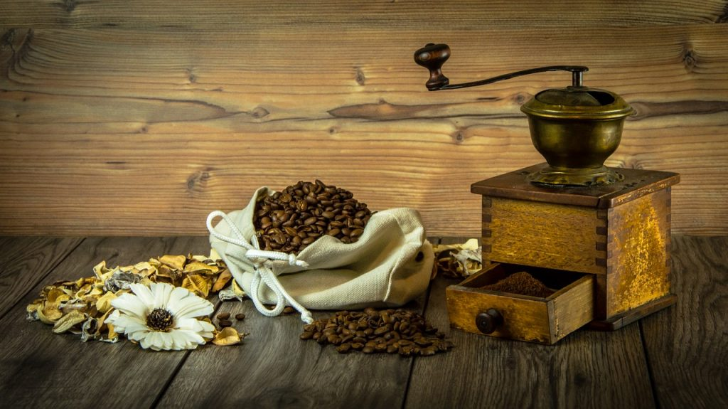 Coffee beans and a hand coffee grinder.