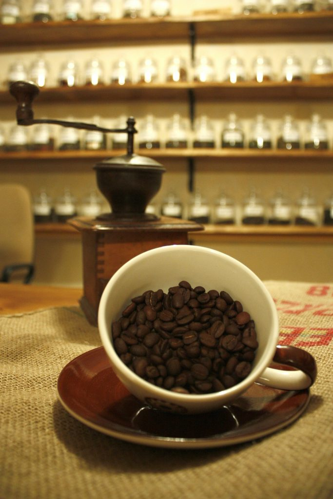 A coffee cup pouring over with beans and a coffee grinder in the background.