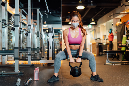 Which is More Beneficial: Training in the Home or Training in the Gym? Woman workout with equipment