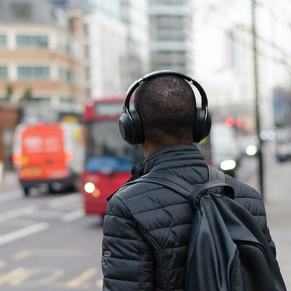 A man wearing black headphones crossing a busy street.
