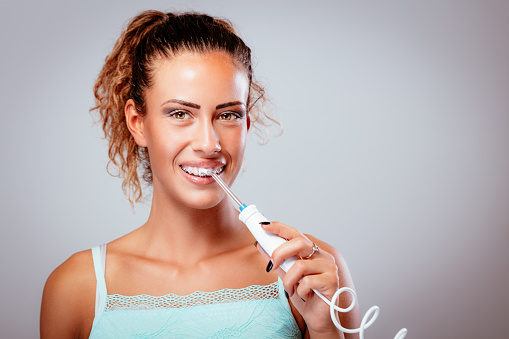 How to Use a Water Flosser. Woman with braces uses flosser to clean teeth