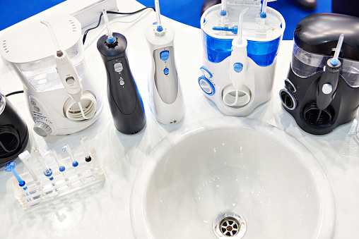How to Use a Water Flosser. A variety of water flossers around a sink