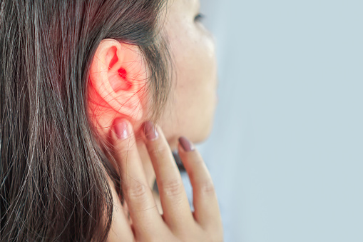 How Much Headphone Use is Too Much. Woman suffers from ear pain