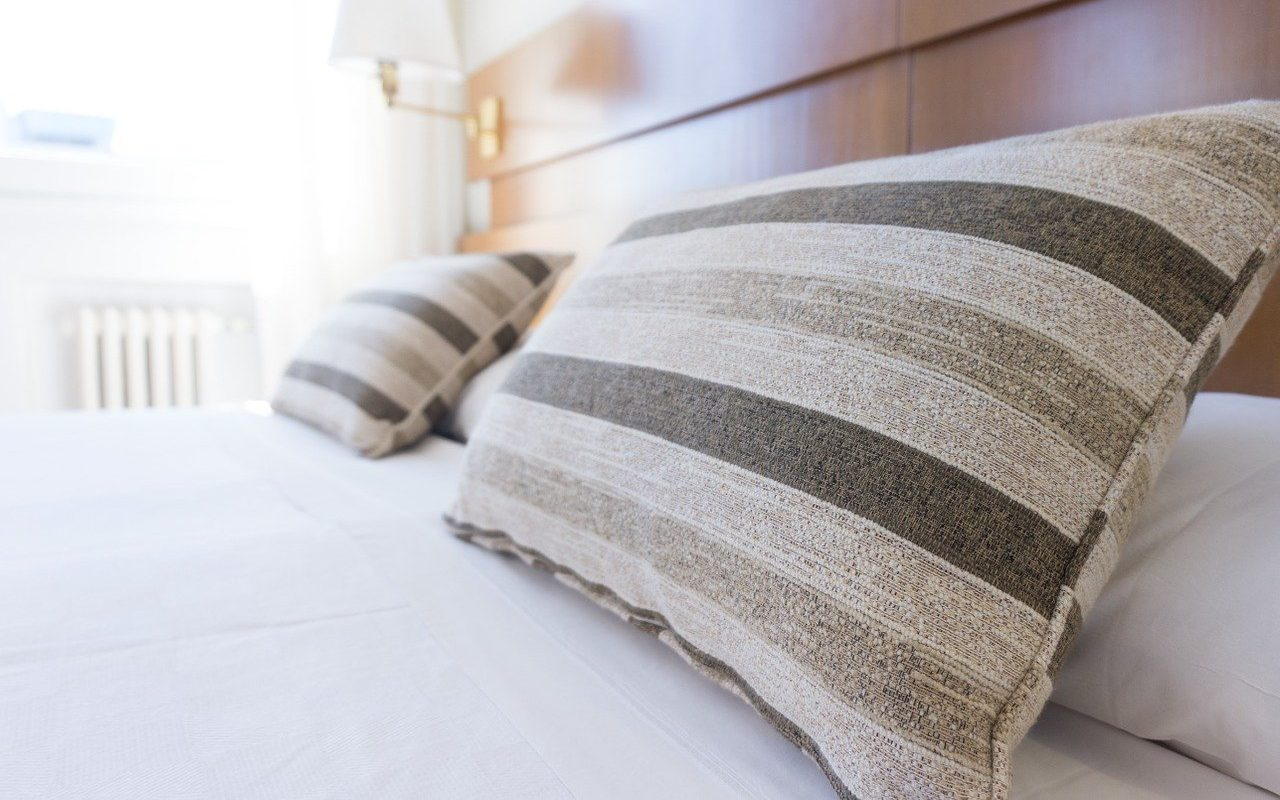 Striped pillows at the head of the bed