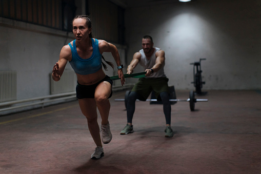 Which is More Beneficial: Training in the Home or Training in the Gym? Man helps woman by safely working out