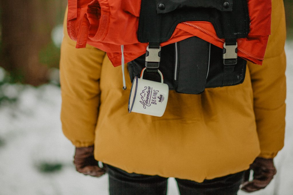 A person wearing a yellow jacket and a backpack with a mug hanging from it.