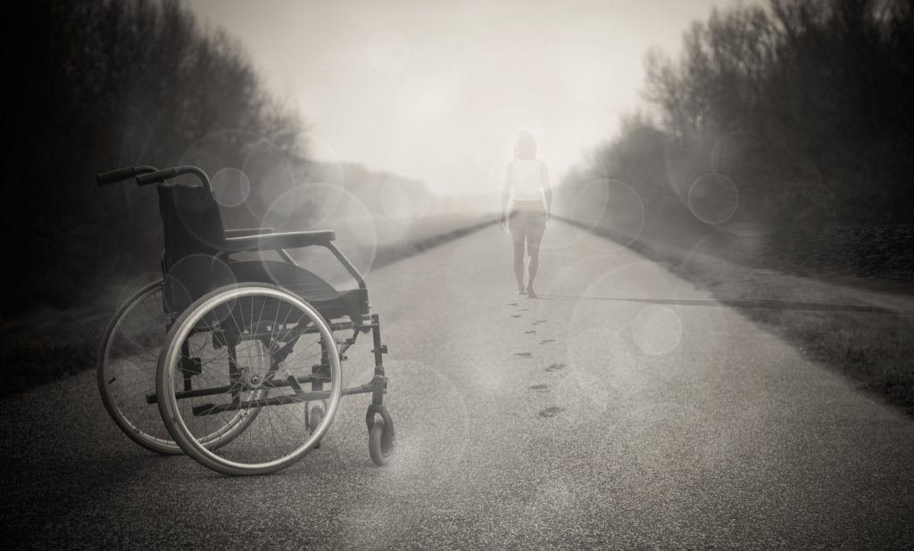 A picture of a person walking away from a wheelchair.