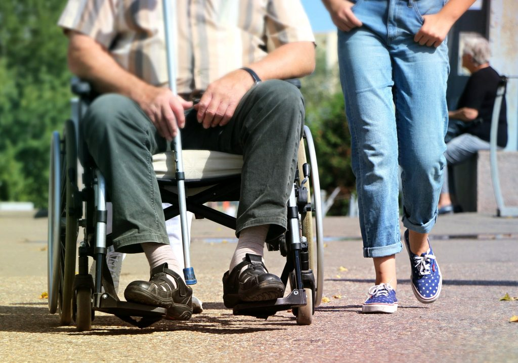 A person in a wheel chair and a person side by side.