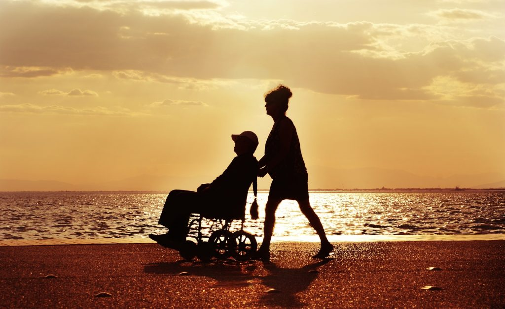 A woman pushing an elderly man in a wheelchair.