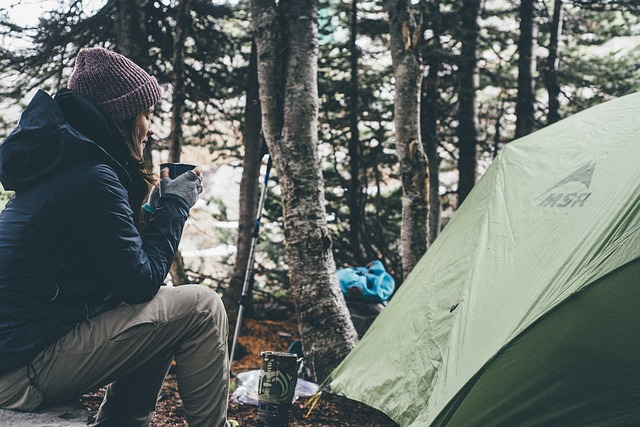 A person sitting by their tent with a cup of coffee.