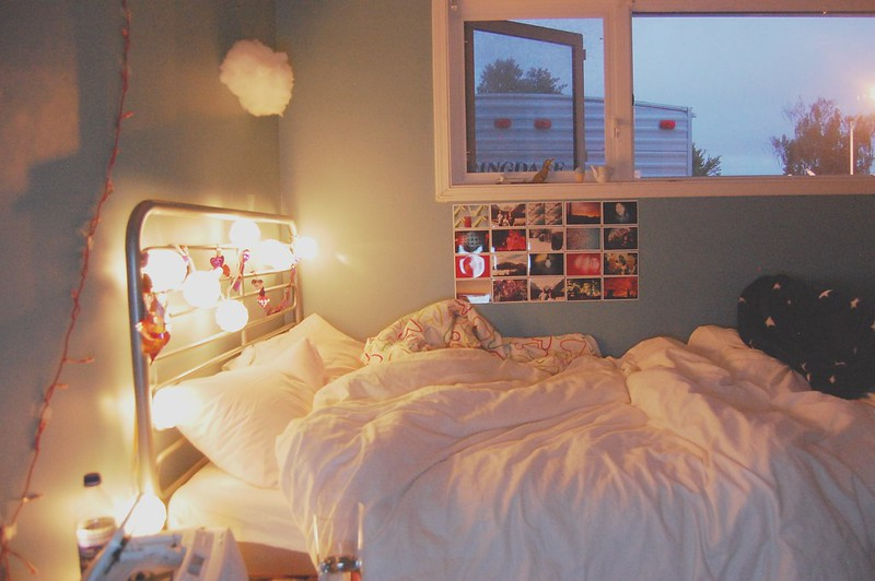A white bed with party lights.