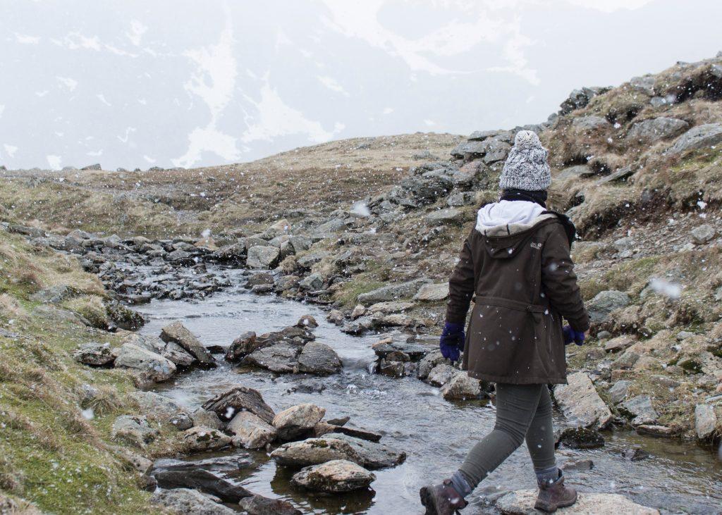 A person walking across a river.