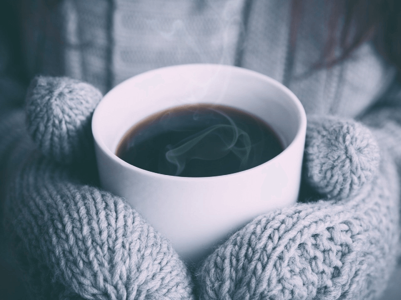 a person with mittens holding a mug of steaming coffee.