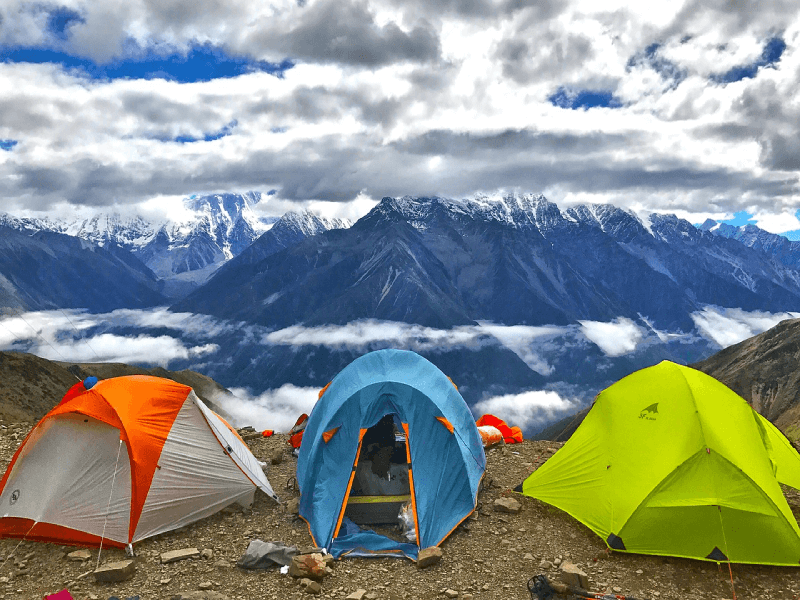 Three tents set up in the mountains