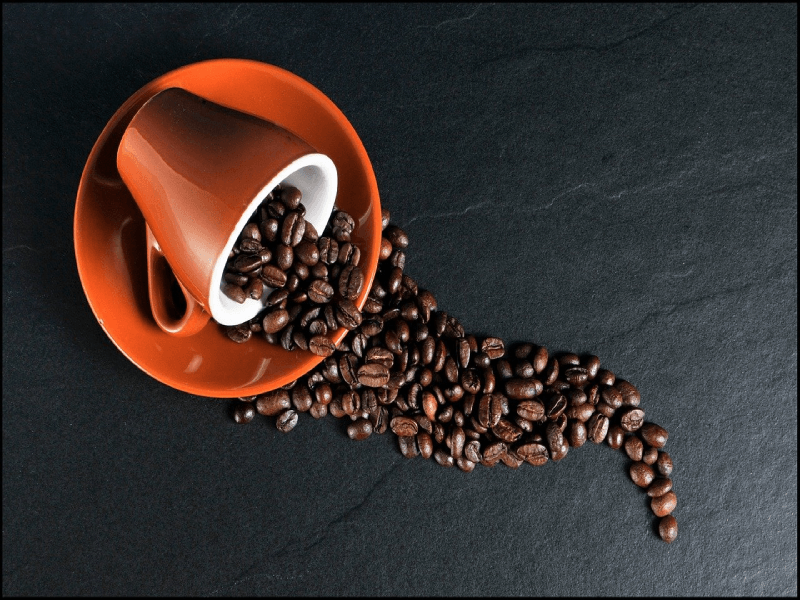 Coffee beans spilling from a coffee cup laying on plate