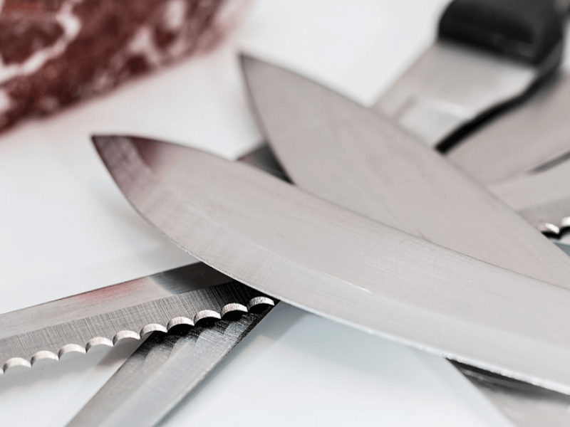 how to maintain a sharp knife  Serrated knife with multiple kitchen knives placed on top of each other