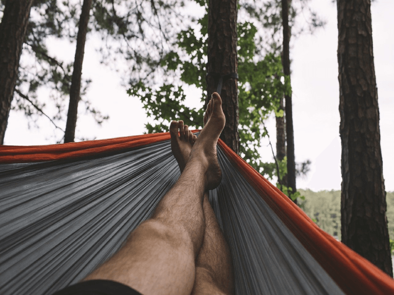 Man's legs and feet in a gray and red hammock in the forest