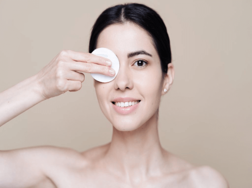 Caucasian women removing eye makeup and mascara with a cotton pad