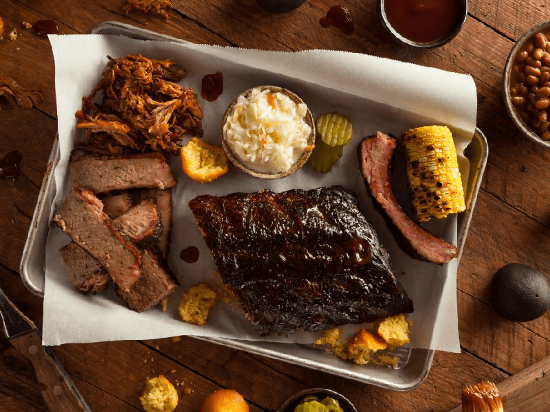 Beef platter including brisket, rips and sides like fried onion, coleslaw, pickles, corn, and cornbread