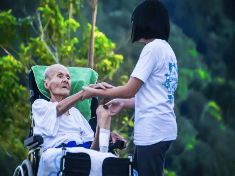 girl helping elder in wheelchair